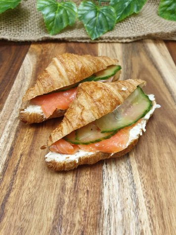 Mini croissant filled with caper cream cheese, smoked salmon, and pickled cucumber